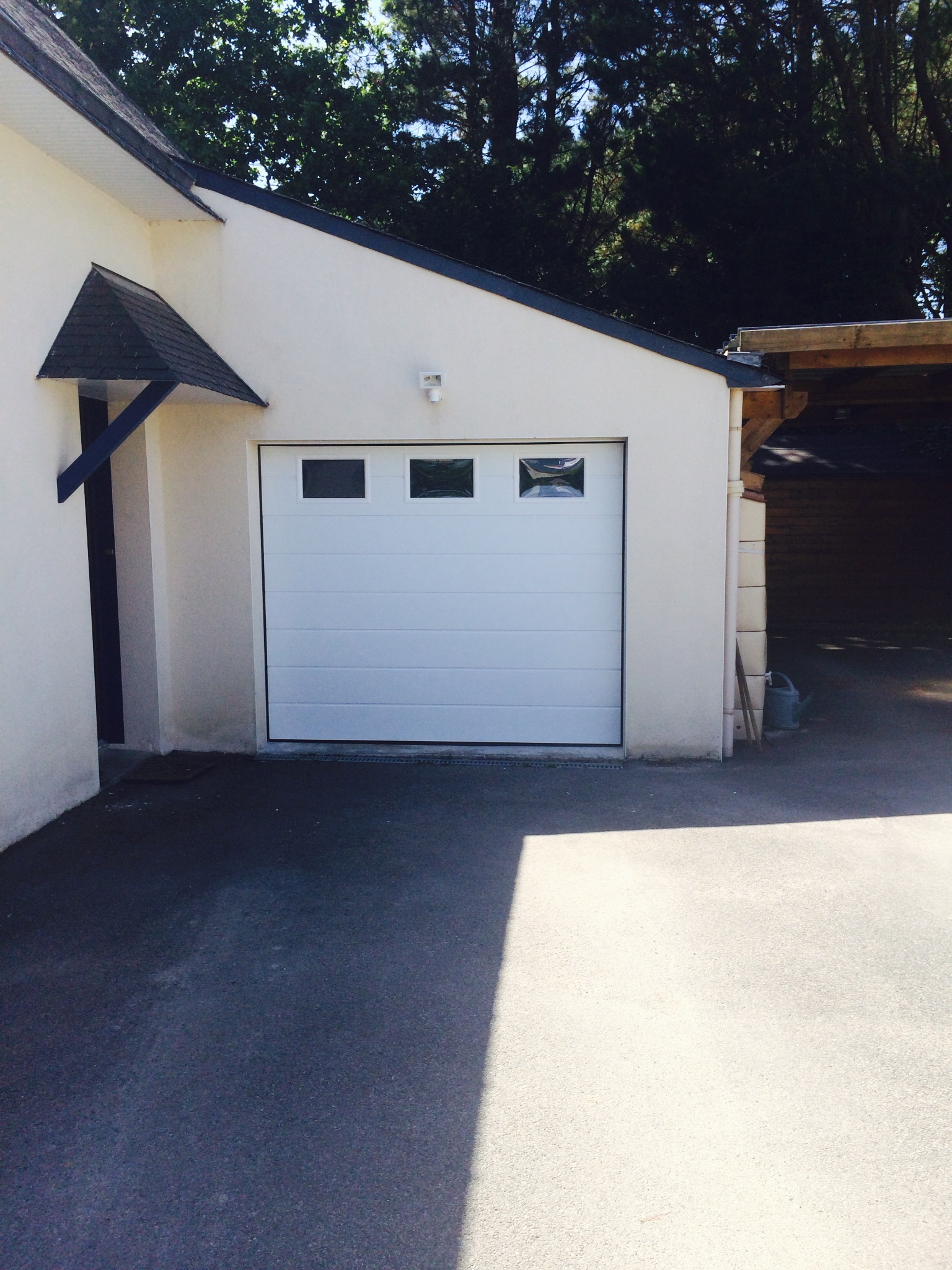 Porte de garage sectionnelle avec hublot réalisée à Pluneret